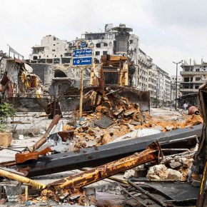 A bulldozer removes debris at al-Hamdeya neighborhood in Homs city May 9, 2014.