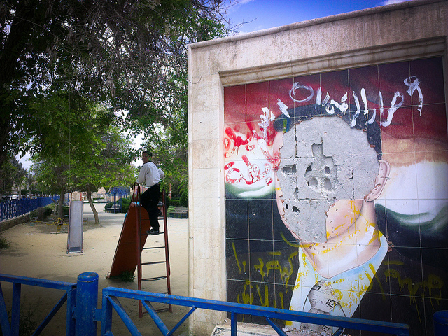 Defaced Assad mural. Raqqa playground, 2013.
