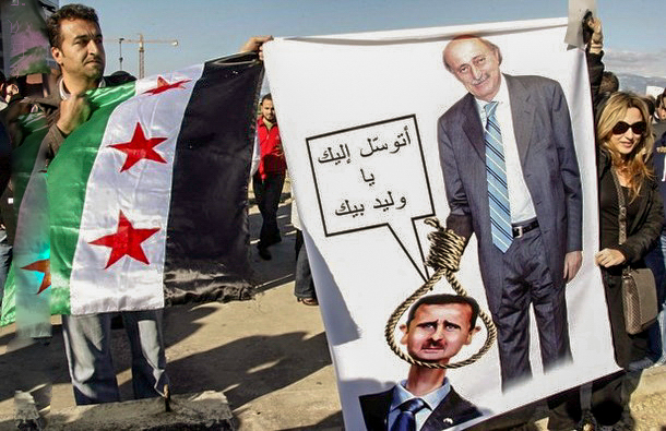 Demonstrators carry a Syrian opposition flag and a caricature depicting Lebanon's Druze leader Walid Jumblatt holding a noose around the neck of Syria's President Bashar al-Assad, during a protest in Martyrs Square in Beirut.